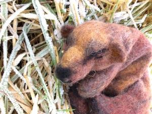 Brown bear in garden, made out of felt