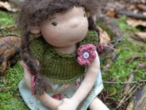 Little girl doll sat in the woods