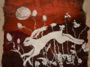 Felted hare jumping across the fields