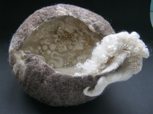 """""""Inner Beauty""""<br/>A combination of wet felting and needle felting with embroidery incorporating satin and other fabrics and textures with Jacobs fleece for the bowl's exterior."""