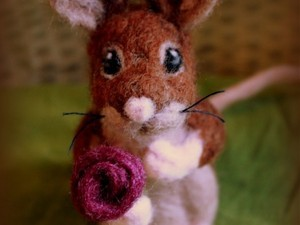 Felted mouse holding a rose