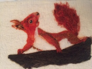 A Red Squirrel Using Orange, White And Brown Merino Wool