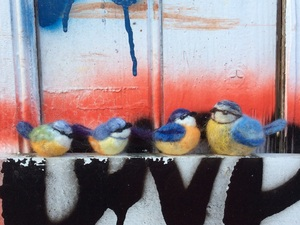Felted yellow and blue birds on ledge