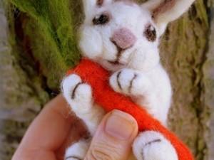 White rabbit holding carrot made out of felt