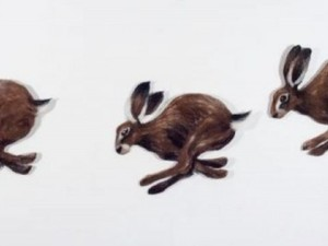 Felted hares running in a line